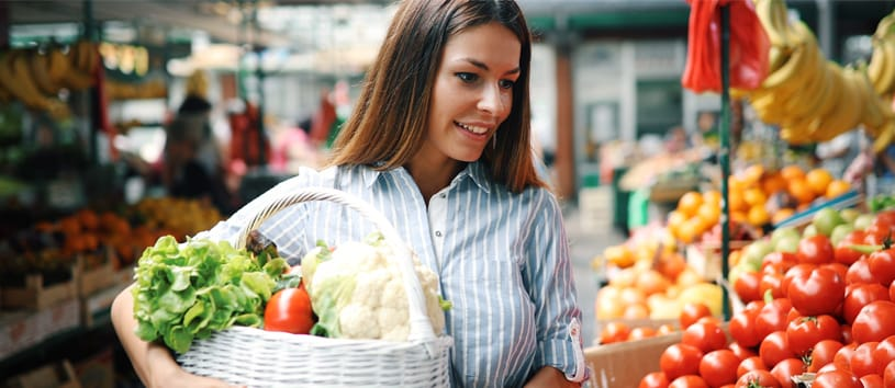 woman holding groceries basket full of vegetables