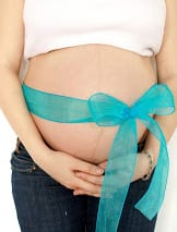 Pregnant woman's belly with a bow wrapped around it