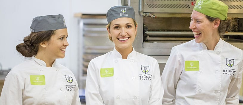 Three Natural Chef students at Bauman College are smiling & laughing in the kitchen