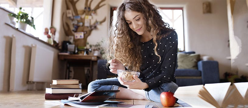 Woman sitting on floor of her home eating breakfast and studying