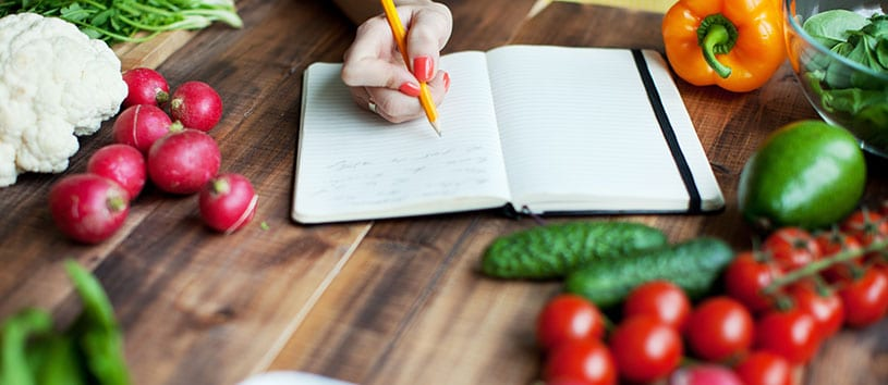 Someone, possibly a Natural Chef and Nutrition Consultant student at Bauman College in California, is writing in a book on a wooden table with delicious-looking fresh veggies all over it