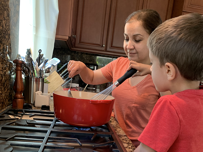 Bauman College graduate Paty Stewart, cooking with her son